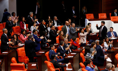 Pro-Kurdish opposition Peoples' Democratic Party MPs react after Turkey's parliament approved a bill to lift lawmakers' immunity from prosecution, at the Turkish parliament in Ankara