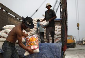 Roni, an Indonesian worker unloads a sack of rice from a truck in Sunda Kelapa port in Jakarta