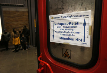 Illegal immigrants stand nextto the night train from Budapest to Munich after their arrival at Munich central railway station