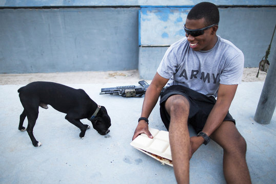 Private First Class Berryman laughs as he grabs his meal from therapy dog Hank at Combat Outpost Nangalam in Afghanistan