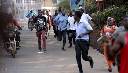 People run on a street during clashes between opposition supporters and security forces in Kampala
