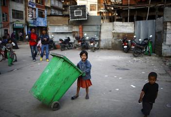 A girl plays with a garbage bin in Kathmandu