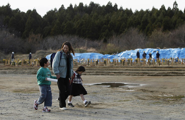 Wakana Kumagai, 6, visits the grave of her father, who was killed by the March 11 tsunami, with her mother Yoshiko and brother Koki at a temporary mass grave site in Higashi-Matsushima