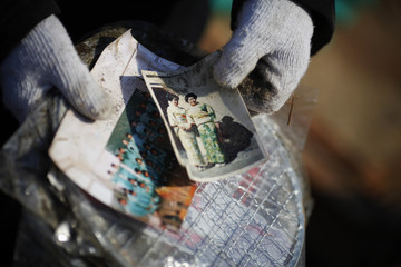 Hideko Tanaka holds a photo of herself and her sister Yuko found in the ruins of a family home in Yamada