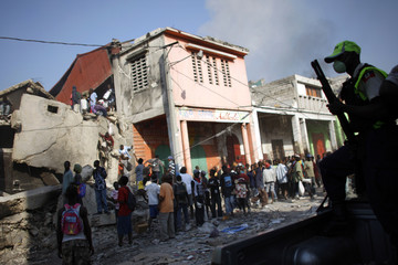 Looters enter a destroyed store as Haitian police drive past in Port-au-Prince