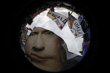 Supporters of Russian PM Putin wave flags in a picture taken with a fisheye lens before a rally in central Moscow