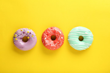 Tasty donuts with sprinkles on yellow paper background