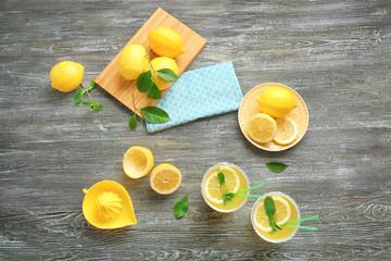 Glasses of lemon juice on wooden background