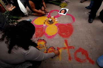 Activists draw a flower on the floor with chalk as part of a makeshift altar for slain environmental rights activist Berta Caceres during a protest outside the morgue in Tegucigalpa