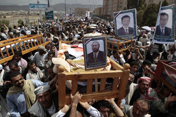 Anti-government protesters carry the bodies of fighters loyal to opposition tribal chief Sheikh Sadiq al-Ahmar during a mass funeral in Sanaa
