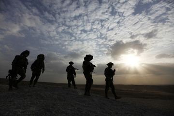 Israeli soldiers walk with their weapons during a drill at a base south of Hebron