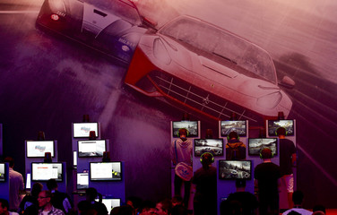 Visitors play Need for Speed Rivals game at the Electronic Arts EA exhibition stand during the Gamescom 2013 fair in Cologne