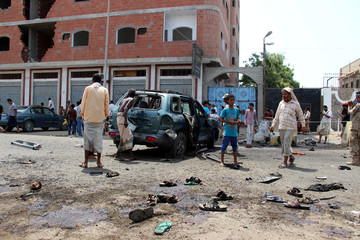 People check the site of a suicide bombing in the southern port city of Aden, Yemen