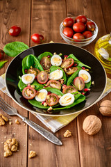 Fresh vegetable salad with spinach, cherry tomatoes, quail eggs, pomegranate seeds and walnuts in black plate on wooden table.