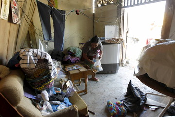 People pick their belongings up among debris at their house in Jama