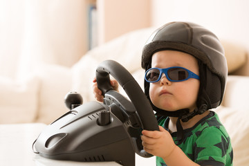 Cute little kid boy in a helmet playing with Computer steering wheel. Future driver. Getting ready for professional driving. Child driving a car. Funny toddler boy indoors. Boy and a car.