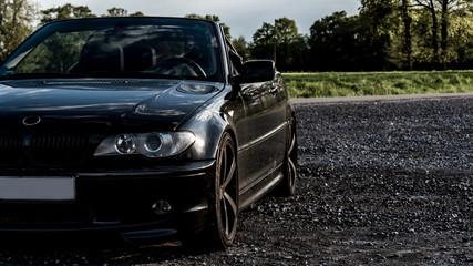 Schwarzes Cabrio mit 19° Alufelgen auf Schotterplatz