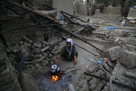 A survivor of an earthquake prepares tea as he is surrounded by rubble of his mud house after it collapsed following the quake in the town of Mashkeel