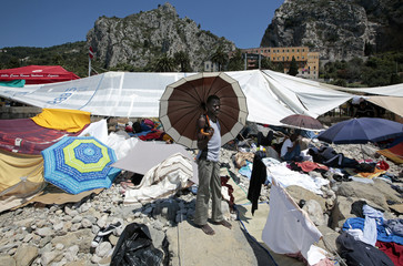 Migrants shelter from sun under tents and umbrellas on the rocks of the seawall at the Saint Ludovic border crossing on the Mediterranean Sea between Vintimille and Menton