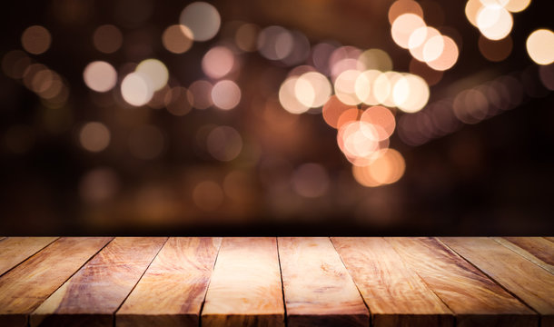 Wood table top with blur light bokeh in dark night cafe,restaurant background .Lifestyle and celebration concept