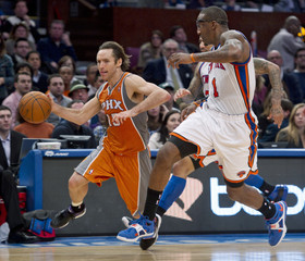 Phoenix Suns Nash drives down the court chased by New York Knicks Stoudemire during their NBA basketball game in New York