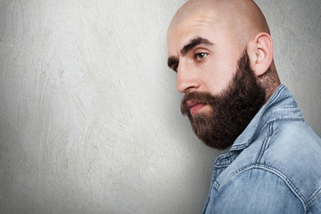 A sideways portraitwith copy space of fashionable bald hipster having tattoo on his neck, thick black eyebrows and beard, big dark eyes wearing jean shirt looking aside. People and lifestyle.