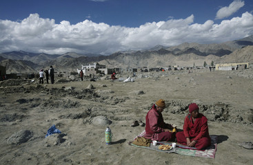 Monks perform religious rites for flash floods victims on the outskirts of Leh, east of Srinagar