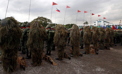Soldiers in sniper camouflage stand at attention before the start of a parade for the change of command for the new Armed Forces chief at a military camp in Quezon City, Metro Manila