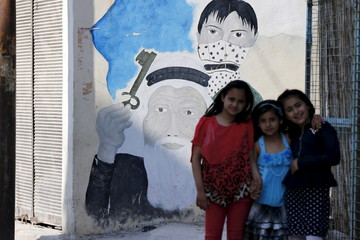 Palestinian refugee children pose as they play at Al-Baqaa Palestinian refugee camp