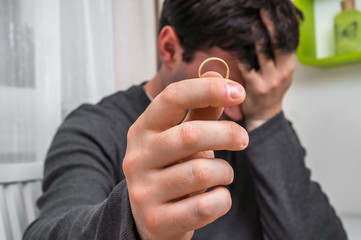 Man is holding wedding ring - divorce concept