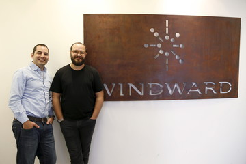 Matan Peled and Ami Daniel, former Israeli navy officers and founders of Windward, an Israeli maritime data and analytics company, pose for a picture near their company logo at their offices in Tel Aviv, Israel
