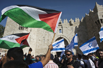 Palestinian protesters wave Palestinian flags as Israelis carrying Israeli flags walk past outside Jerusalem's Old City during a parade marking Jerusalem Day