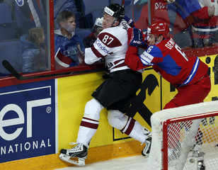 Russia's Denisov checks Latvia's Meija against the glass during their 2013 IIHF Ice Hockey World Championship preliminary round match at the Hartwall Arena in Helsinki