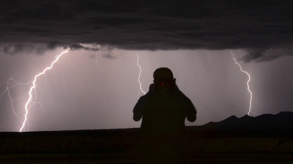 Storm chaser photographer Mike Meadows is silhouetted as lightning strikes outside Lake Havasu City