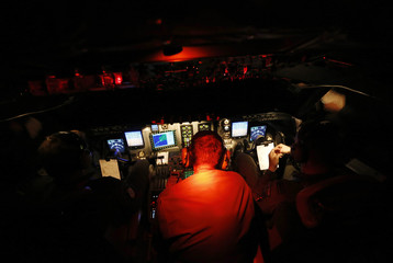 Pilots and engineers sit in the dark cockpit of a Royal New Zealand Air Force P-3K2 Orion aircraft as they return at night from the search for missing Malaysian Airlines flight MH370