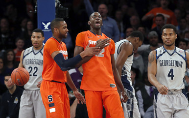 Orange's Keita celebrates with his teammate Southerland as Hoyas' Porter Jr. and Smith-Rivera look on, during their NCAA men's college basketball semi-final game at the 2013 Big East tournament in New York