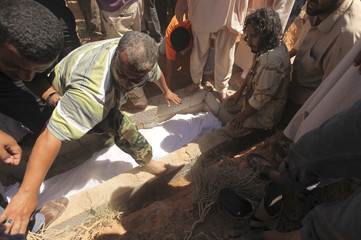 Libyans bury the body of a rebel after an ambush by pro-Gaddafi forces on Monday targeting an oil refinery in Ras Lanuf, during his funeral in Benghazi