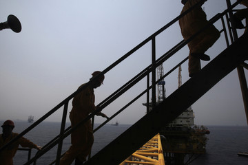 """Employees walk up a staircase in the production area at the Mexico's state-run oil monopoly Pemex platform """"Ku Maloob Zaap"""" in the Northeast Marine Region of Pemex Exploration and Production in the Bay of Campeche"""