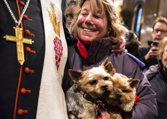 """An owner smiles as she has her pet dogs blessed by a church official during the """"Blessing of the Animals"""" at the Christ Church United Methodist in Manhattan, New York"""