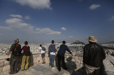 Tourists enjoy the view atop the Acropolis hill in Athens