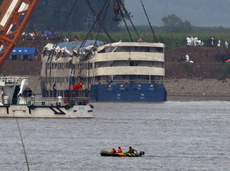 A rescue team works on lifting the capsized cruise ship Eastern Star in the Jianli section of Yangtze River, Hubei province