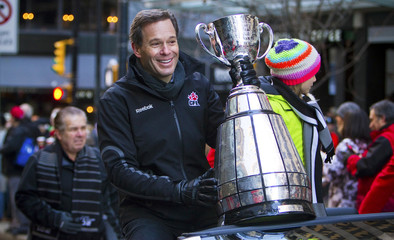 CFL Commissioner Mark Cohon holds the Grey Cup during the 102nd Grey Cup parade in Vancouver