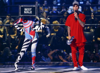 """Canadian singer Bieber holds the """"Best Male"""" award during the MTV EMA awards at the Assago forum in Milan"""