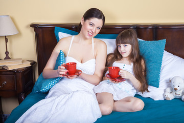 Happy mother and daughter having fun and holding cup and resting in bed, looking at camera and smiling.