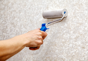 man's hand smoothing the wallpaper with a roller closeup