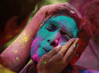 Man reacts as coloured powder is applied while celebrating Holi in Mumbai