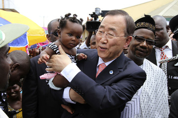 U.N. Secretary General Ban Ki-moon carries a baby after unveiling a primary health care clinic in Dutse Makaranta village, on the outskirt of Nigeria's capital Abuja