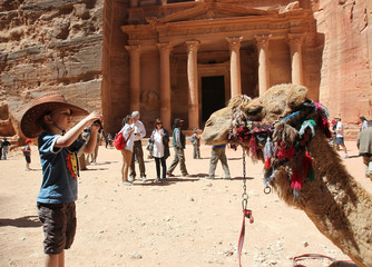 A tourist boy takes a picture of a camel at the Red Rose ancient city of Petra