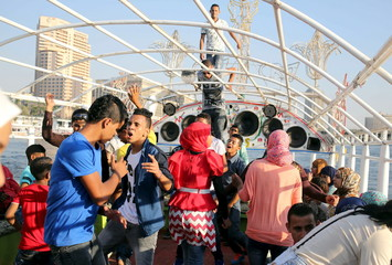 Young people dance during a Nile cruise during celebrations for Eid, which marks the end of the holy fasting month of Ramadan, in Cairo, Egypt