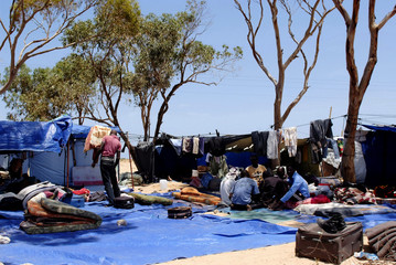 Libyan refugees sit on the ground at the Shousha camp where they have lost their belongings after violent clashes, at Ras Jdeer border in Tunisia